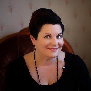 Sari Kaasinen hymyilevänä tummanpunaisessa nojatuolissa.