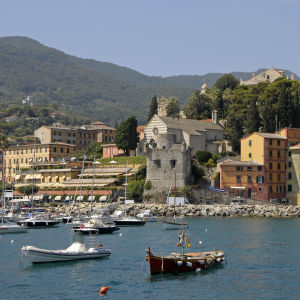 Båtar ligger vid en strand med en stad med färggranna stenhus i bakgrunden samt höga berg.