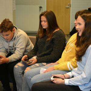 Niorna Alex Östman, Amanda Nyby, Matilda Bengts och Emilia blom sitter i en soffa och ser på sina telefoner.
