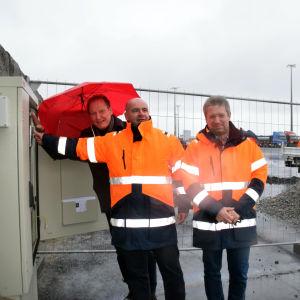 Tre män, två har reflexjackor, en håller i ett paraply. En av männen i reflexjacka trycker på en knapp.