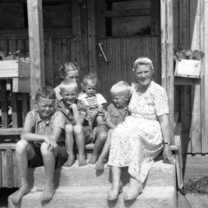 Aili Mäkelä sisrensa ja poikiensa kanssa talon portailla.