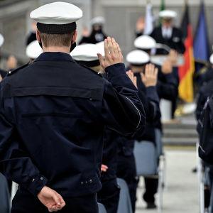 Poliser i Tyskland står med ryggen mot kameran och höger hand upp i luften,
