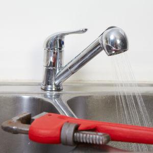 En vatten kran med duschmunstycke som det rinner vatten i en ho från. I förgrunden ligger en röd skiftnyckel.