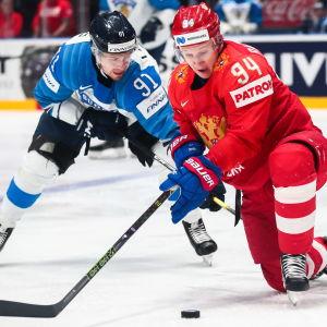 Juho Lammikko och Alexander Barabanov kämpar om pucken i VM-semifinalen 2019.