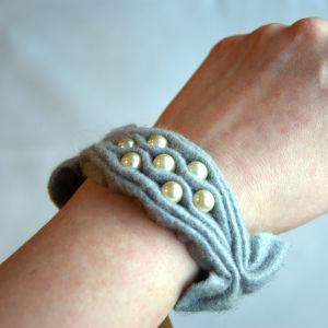 Ett armband av rynkat grått filttyg med pärlbroderi som är knutet runt en handled.