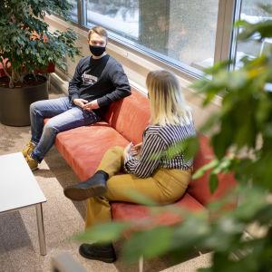 Tekniikan opiskelijat Miika Peltotalo ja Katriina McCormick istuvat Turun yliopiston Agora-rakennuksen aulassa.