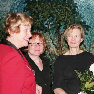 Kolme naista suuren siniturkoosin mosaiikkityön edessä.
