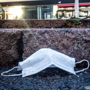 Pois heitetty kasvomaski asfaltilla ostoskeskuksessa.