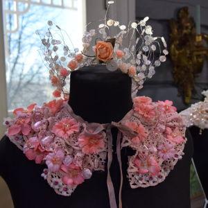 En dekorativ festkrage gjord av gammal, rosa, återvunnen spets och dekorerad med tygblommor och pärlor i olika rosa nyanser. Kragen kan användas till maskerad eller fest och är knuten runt halsen på en svart provdocka.