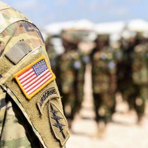 I förgrunden syns en soldats arm varpå man ser USA:s flagga på uniformen. I bakgrunden syns ännu fler soldater i uniform i Somalia.