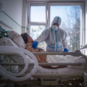 En sjuksköterska tar hand om en patient på en avdelning för coronasmittade på Koranyi-sjukhuset i Budapest. Bilden tagen den 8 april.