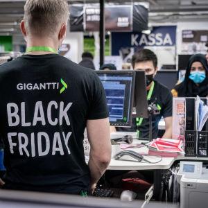 Gigantin myyjä Black Friday t-paidassa myymälässä.