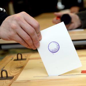 En person sätter röstsedeln i valurnan.
