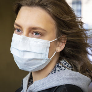 Kvinna iklädd munskydd fotogragerad i sidoprofil.