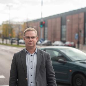 Direktören för den svenska servicehelheten vid sektorn för fostran och utbildning, Niclas Grönholm, står ute framför en väg. Det är höst. En bil kör förbi, Grönholm ser allvarsam ut och tittar åt höger.