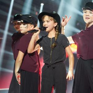 Sofie på MGP-scenen med svart hatt och dansare i bakgrunden.