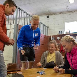 Fyra personer spelar ett spel vid ett bord inne i ett stall.