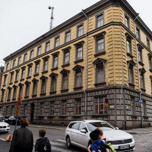 Stenhus i fyra våningar. Fasaden är gul frånsett första våningen som är grå. us i Rödbergen i Helsingfors. Fasaden är gul. Skyddspolisens högkvarter i Helsingfors.