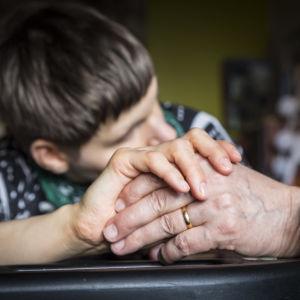 En flicka med funktionsnedsättning håller i sin pappas hand.