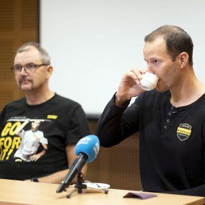 Tero Pitkämäki dricker kaffe och Hannu Kangas tittar framåt.