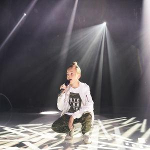 Hugo käld står på huk och sjunger som gästartist under MGP 2018.