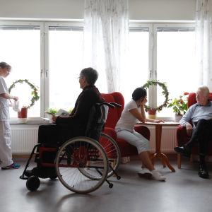 Två personer sitter i var sin fåtölj och samtalar. På bilden finns också en person i rullstol och en person som står vid ett fönster och vattnar en växt.