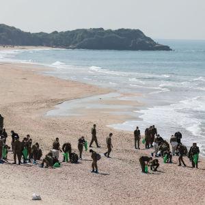 Soldater som arbetar med att rengöra en strand