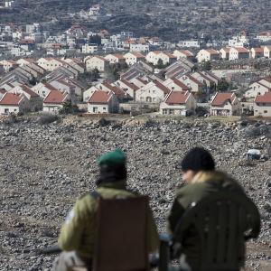 Kuvassa kaksi israelilaispoliisia valvoo etäältä Ofran siirtokuntaa Länsirannalla.