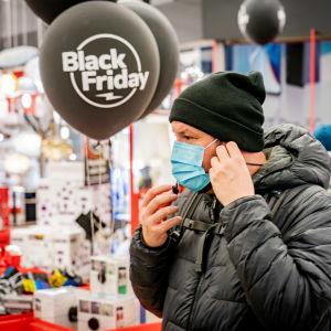 En person i ansiktsmask vid ingången till en butik under Black Friday.