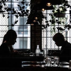 Några människor som sitter och äter på restaurang.