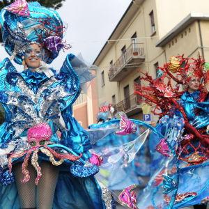 Karnevaaliasuisia henkilöitä, joiden vedensinisissä puvuissa koristeena mustekaloja, koralleja, perhoskaloja. Viareggio, Italia.