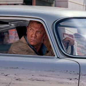 Närbild på James Bond (Daniel Craig) som kör bil och ser bekymrad ut.