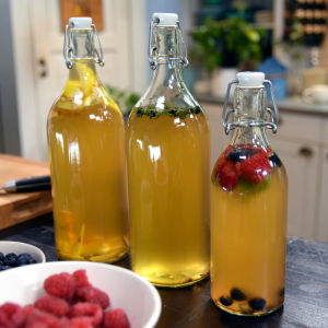 Tre glasflaskor med gul kombucha i.