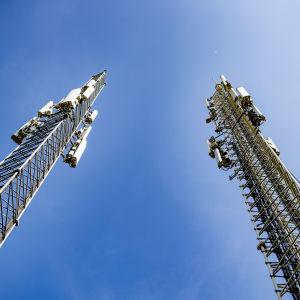 Två höga 5G-master mot en blå himmel.
