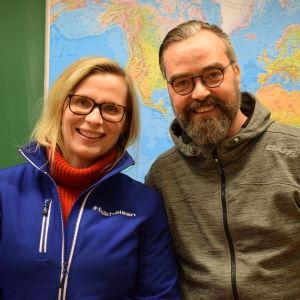 Sabina och Micke framför en världskarta i ett klassrum.