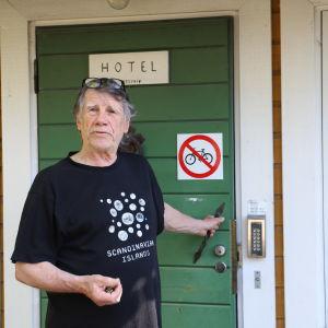 Man står utanför huset och håller i handtaget till en grön dörr.