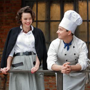 Karaktärerna Nina och Calle står på restaurangens bakgård och ler åt varandra.