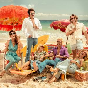 Iloinen 70-lukulaisesti pukeutunut perhe beachillä Australiassa..