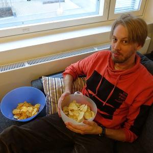 Chipsbloggaren Mikael Hästö sitter i soffan med två chipsskålar i famnen.