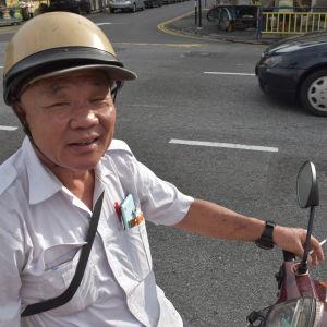 Lee Tion Lai sitter på en moped, med en cigarett i handen.