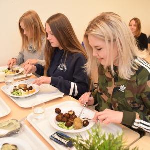 Matilda Hellström, Julia Kallioinen och Ida Bäckström äter fiskbullar och potatis i Källhagens skolas matsal i Virkby.