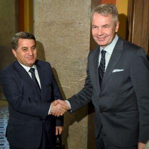 Två män i kostym skakar hand.