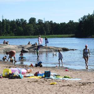 Människor leker och umgås vid sandstranden på Sandudden i Helsingfors.