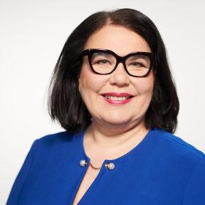 Bild på Yles vd Merja-Ylä Anttila. Hon är klädd i blått och bär glasögon.
