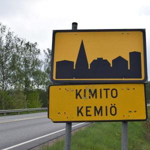 Svartgul vägskylt för tätort med texten Kimito, Kemiö.