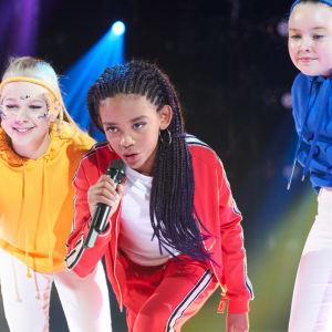 Alina klädd i vitt och rött och med dansare i bakgrunden.