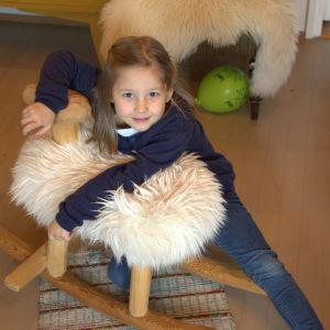 Flicka hänger på en liten gungstol som föreställer ett får.