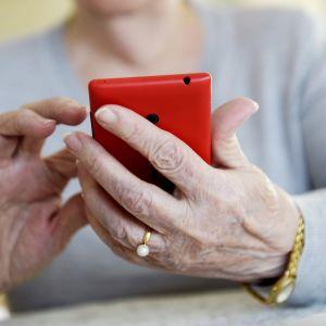 En äldre kvinna håller en röd smarttelefon i handen.