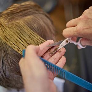 Nuori poika parturi-kampaajalla leikkauttamassa hiuksiaan.