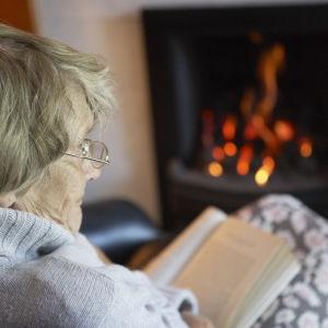 En äldre kvinna sitter och läser en bok framför en öppen spis.